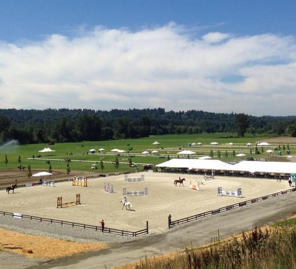 Evergreen Classic Horse Show, at Meadow Wood Equestrian Center, Snohomish, Washington State. The large sand jumper ring, with jumps and jumper riders.